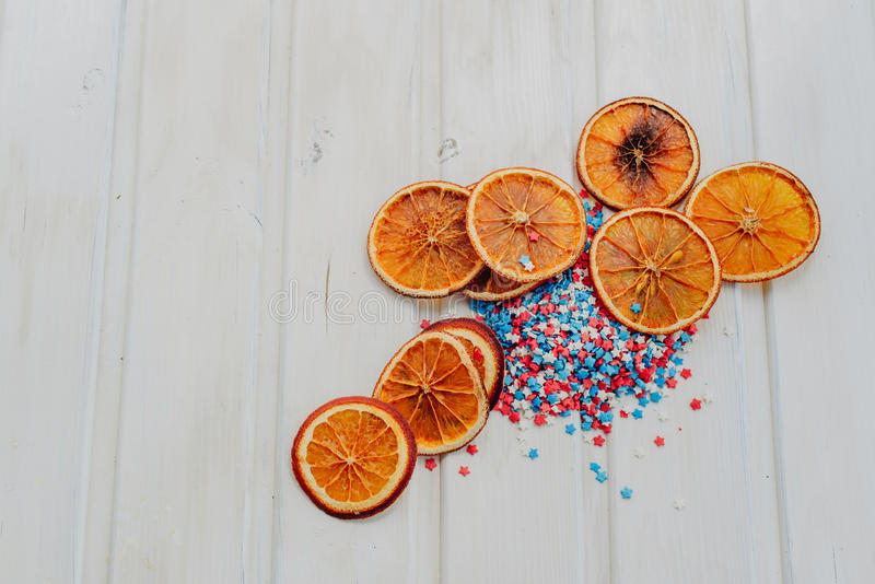 Oranges and stars. Slices of dried oranges and star sprinkles on a white background with copyspace royalty free stock image