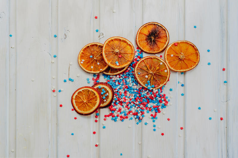 Oranges and stars. Slices of dried oranges and star sprinkles on a white background with copyspace royalty free stock photo