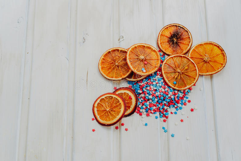 Oranges and stars. Slices of dried oranges and star sprinkles on a white background with copyspace stock photos