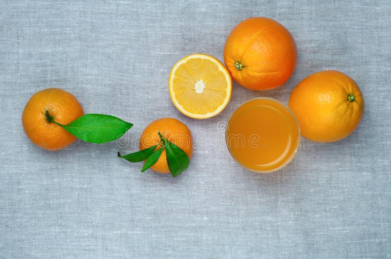 Oranges, tangerines and orange juice in a glass, on a linen tablecloth. Top view. royalty free stock images