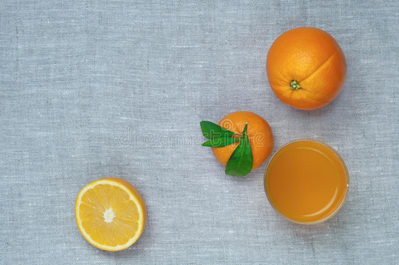 Oranges, tangerines and orange juice in a glass, on a linen tablecloth. Top view. royalty free stock photos