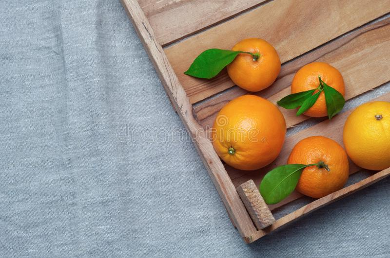 Oranges and tangerines in a wooden box on canvas. Orange juice. royalty free stock image