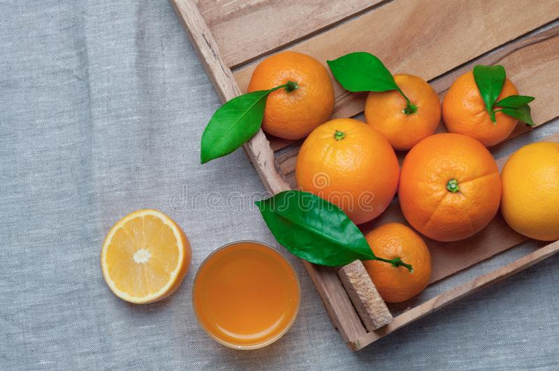 Oranges and tangerines in a wooden box on canvas. Orange juice. stock image