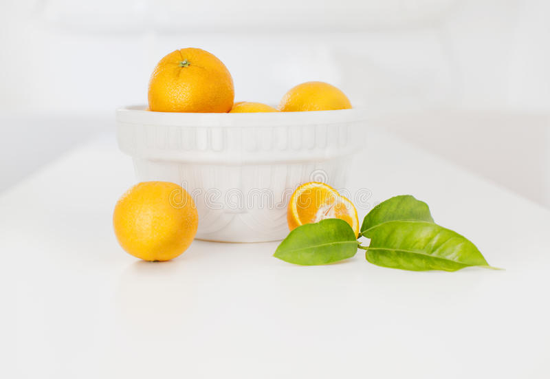 Oranges in a white vase. Still Life in a bright light room stock photography