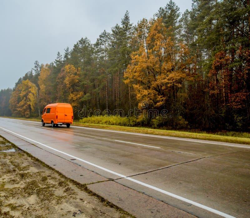 Oranje auto-bestelwagen, die langs de de herfstweg bij zonsondergang gaan stock foto