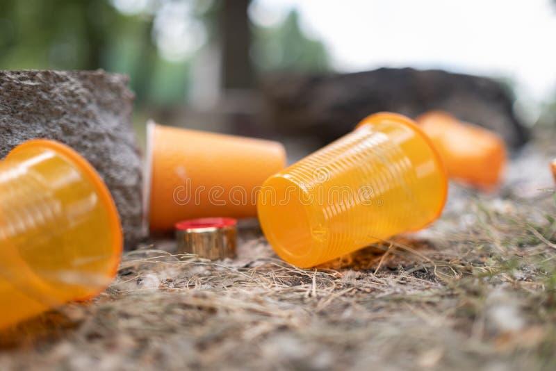 Oranje beschikbare Plastic die glas of koppen voor drinkwater in een bak wordt gebruikt - Milieuprobleemconcept Niet composteerba stock foto's