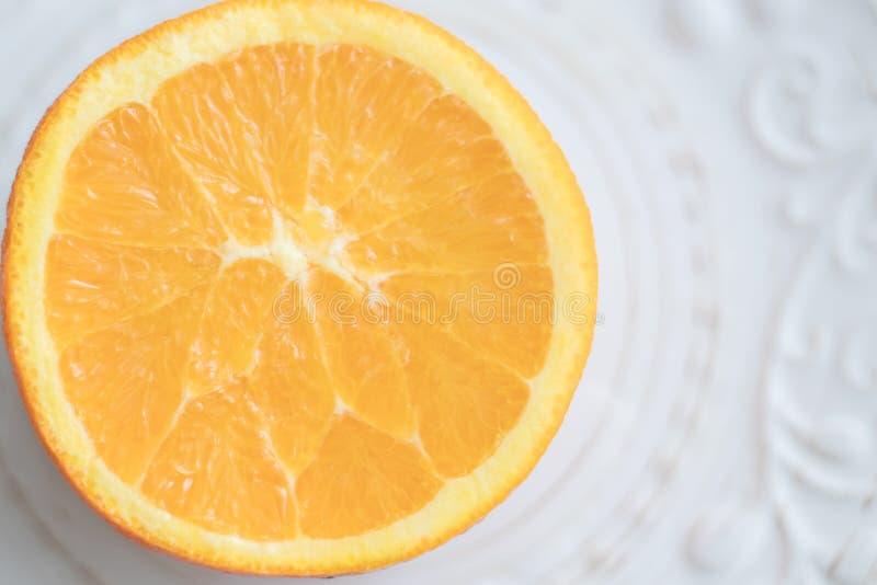 Oranje besnoeiing in halve pulp tot de bovenkant op witte gevormde plaat Hoogste mening De ruimte van het exemplaar royalty-vrije stock foto's