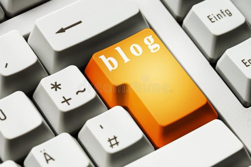 Oranje blogknoop op toetsenbordachtergrond stock fotografie
