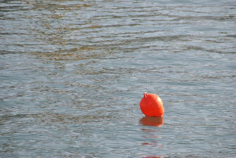 Oranje boei die op het zeewater drijven royalty-vrije stock afbeeldingen