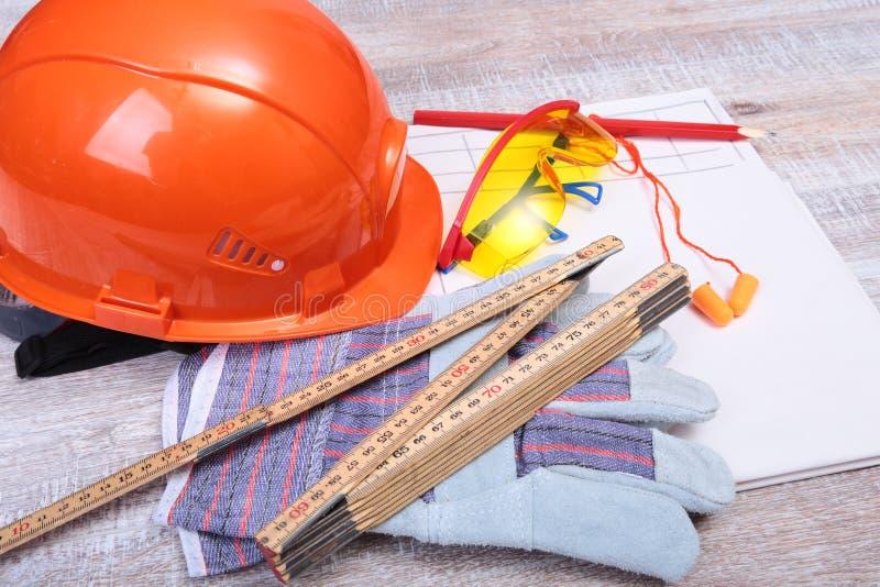 Oranje bouwvakker, oordopje, veiligheidsbril en handschoenen voor het werk Oordopje om lawaai op een witte achtergrond te vermind stock foto