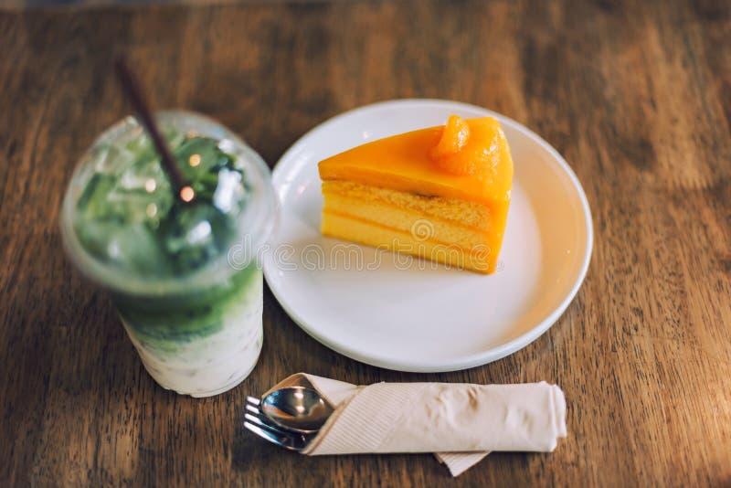 Oranje cake, bevroren matcha groene thee latte met melk en lepel op houten lijst royalty-vrije stock afbeelding