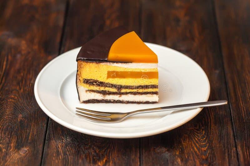 Oranje cake met chocolade op houten achtergrond stock afbeelding