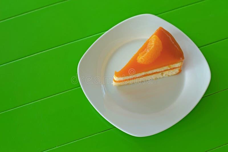 Oranje cake op witte plaat stock foto