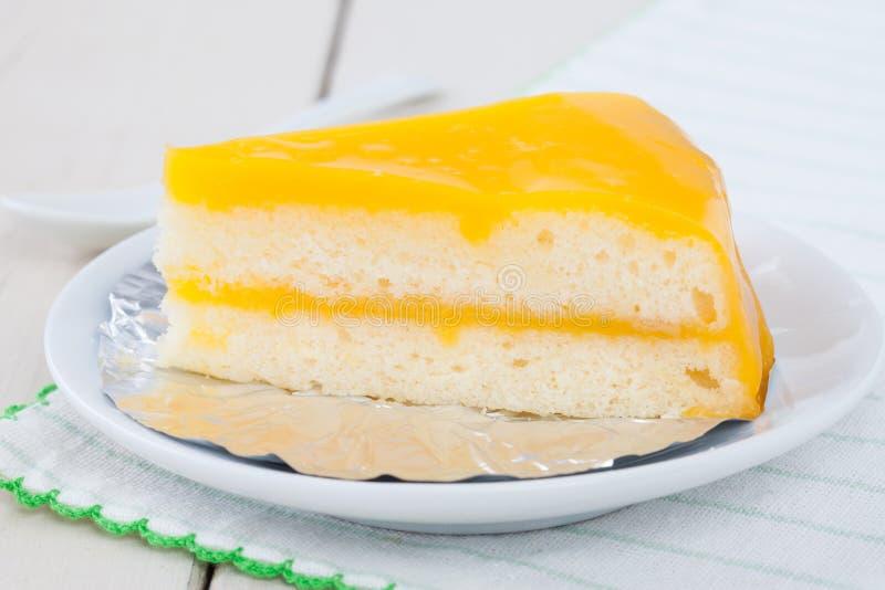 Oranje cake op witte plaat op houten lijst stock foto's