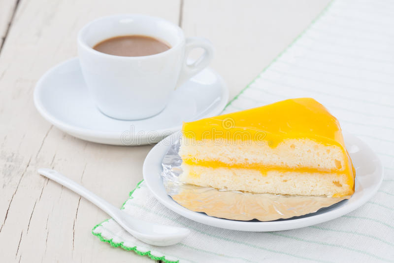 Oranje cake op witte plaat op houten lijst met koffie royalty-vrije stock fotografie