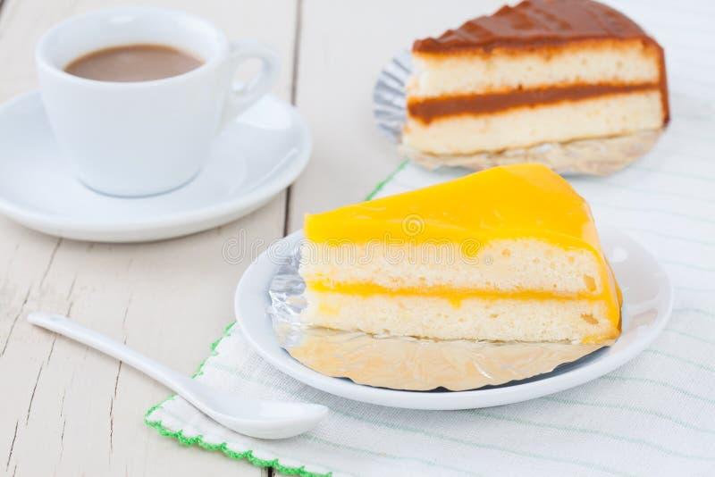 Oranje cake op witte plaat op houten lijst met koffie en coffe stock fotografie
