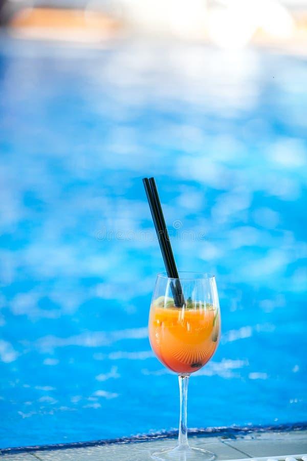 Oranje cocktail op zwembadachtergrond De vakantieconcept van de zomer Verfrissende drank Verticaal schot De ruimte van het exempl stock fotografie