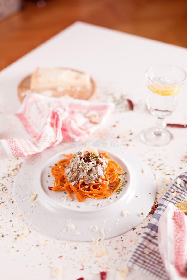 Oranje die deegwaren en witte saus op witte plaat worden gediend stock afbeelding
