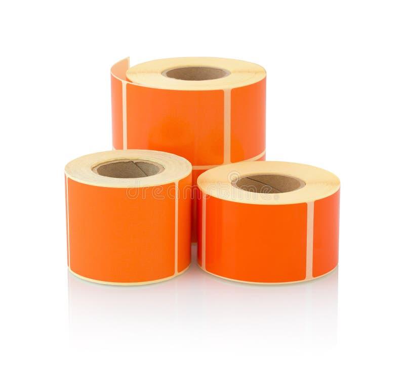 Oranje die etiketbroodje op witte achtergrond met schaduwbezinning wordt geïsoleerd Kleurenspoel van etiketten voor printers stock afbeeldingen