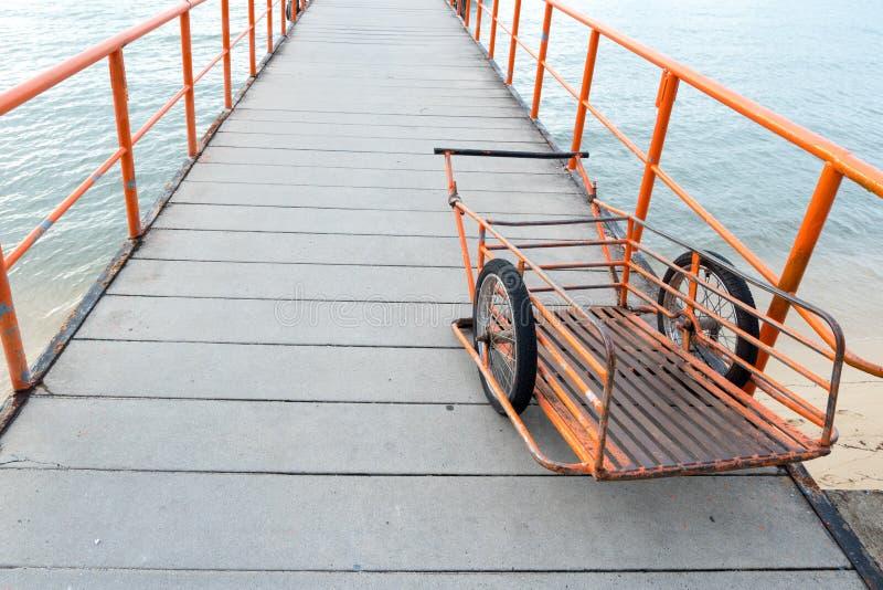 Oranje die stootkar op pijlergang wordt geparkeerd met ijzertraliewerk royalty-vrije stock foto