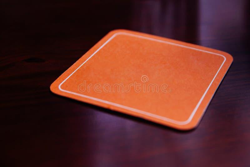 Oranje document onderlegger voor glazen op houten lijst royalty-vrije stock foto's