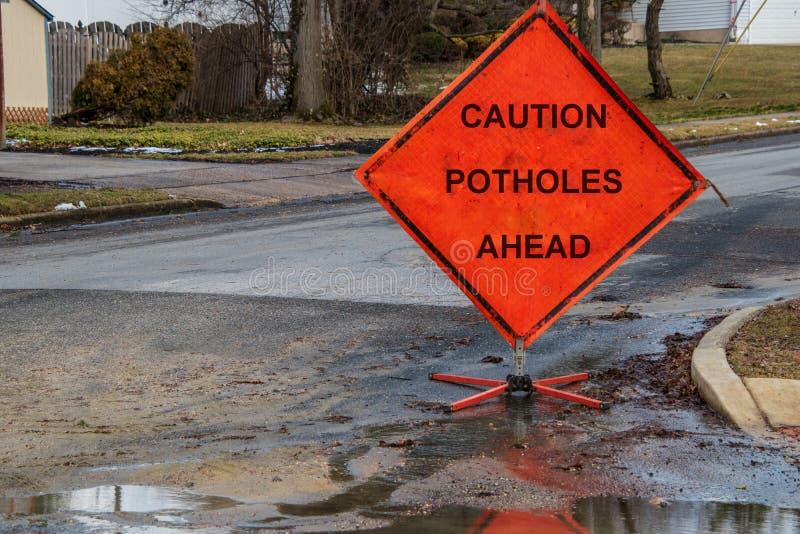 Oranje driehoekige verkeersteken op een kleine straat in de voorsteden die voorzichtigheidspotholes vooruit zegt stock fotografie