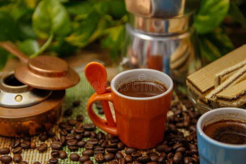 Oranje en blauwe koppen koffie, het koffiezetapparaat van de mokapot, oude alcoholfornuis en koekjes stock foto's
