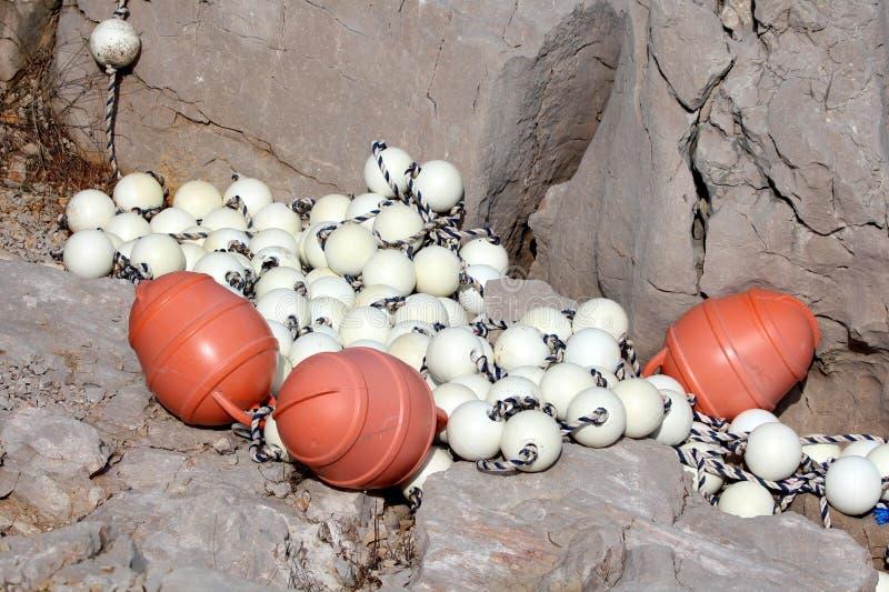 Oranje en witte plastic boeien op sterke die kabel uit overzees over de winter wordt genomen en verlaten op rotsachtig strand royalty-vrije stock afbeelding