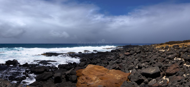 Oranje en zwarte rotsen op oceaankust royalty-vrije stock foto