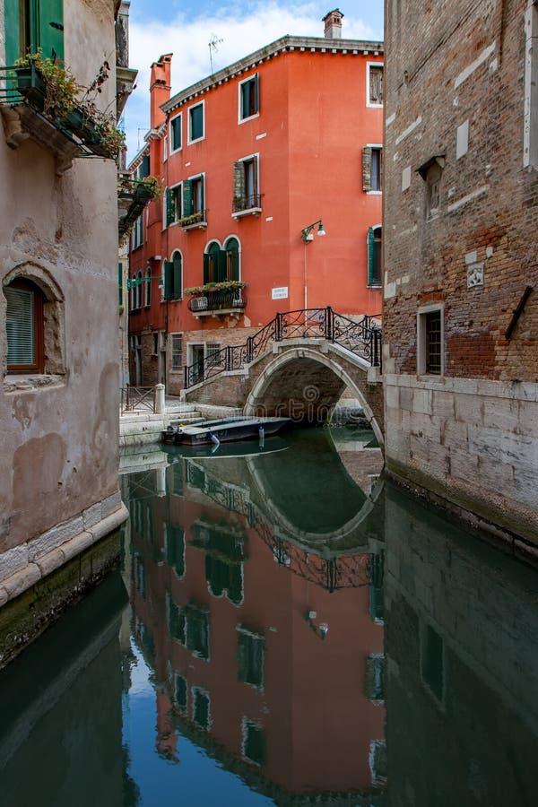 Oranje gebouw en Arching Bridge die in het Kanaal in Venetië reflecteren royalty-vrije stock afbeelding