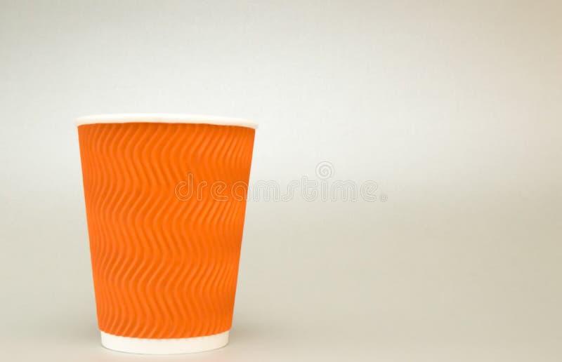 Oranje gecanneleerde document kop voor koffietribunes op witte achtergrond royalty-vrije stock afbeelding