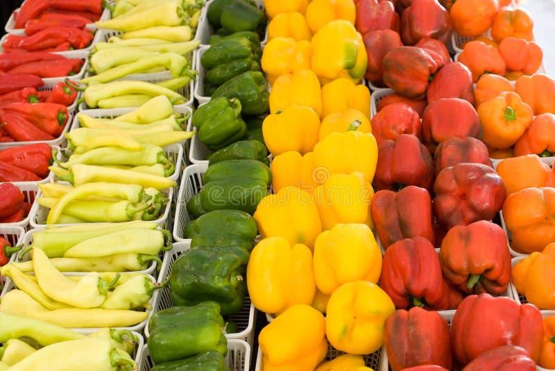 Oranje, gele, groene en Spaanse pepers bij landbouwersmarkt royalty-vrije stock fotografie