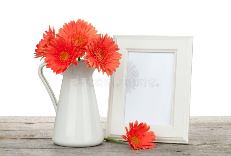 Oranje gerberabloemen en fotokader op houten lijst stock afbeelding
