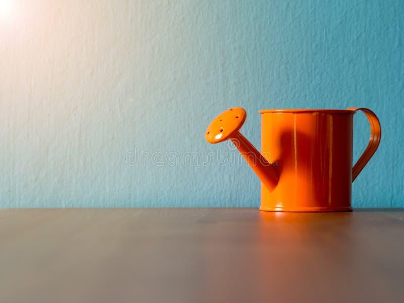 Oranje gieters gezet op houten lijst de achtergrond is turkooise en exemplaarruimte voor inhoud royalty-vrije stock fotografie
