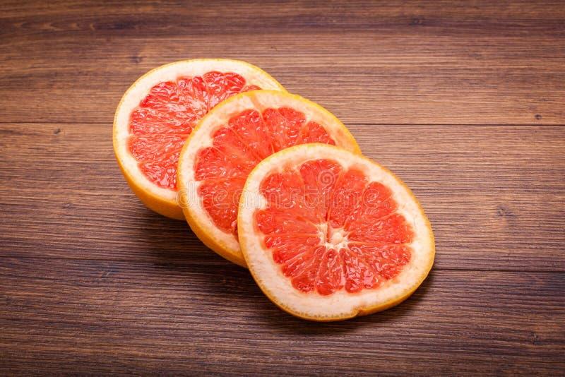 Oranje grapefruit op een houten oppervlakte regeling van gesneden fruit royalty-vrije stock fotografie