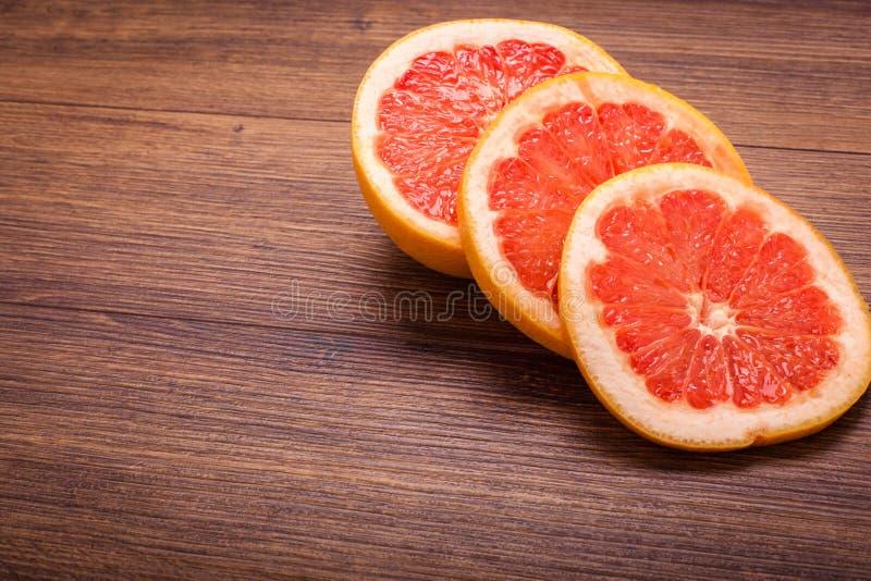 Oranje grapefruit op een houten oppervlakte regeling van gesneden fruit royalty-vrije stock afbeelding