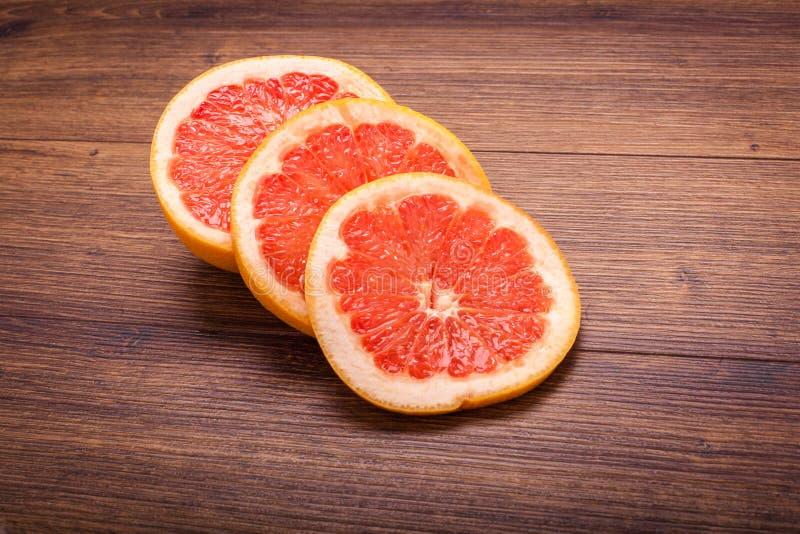 Oranje grapefruit op een houten oppervlakte regeling van gesneden fruit royalty-vrije stock foto