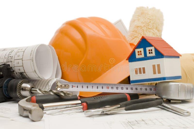 Oranje helm op het huisproject stock afbeeldingen