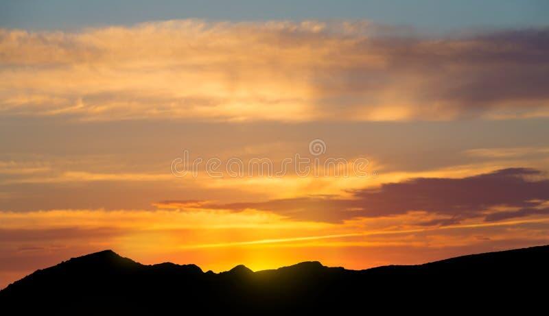 Oranje hemel over silhouetberg in de ochtend stock foto