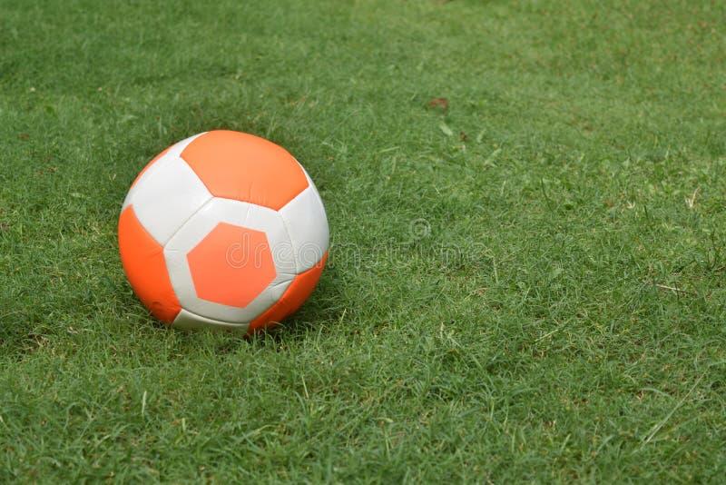 Oranje het gras van het voetbalvoetbal groene exemplaar-ruimte als achtergrond royalty-vrije stock afbeeldingen