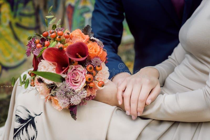 Oranje huwelijksboeket in handen stock fotografie