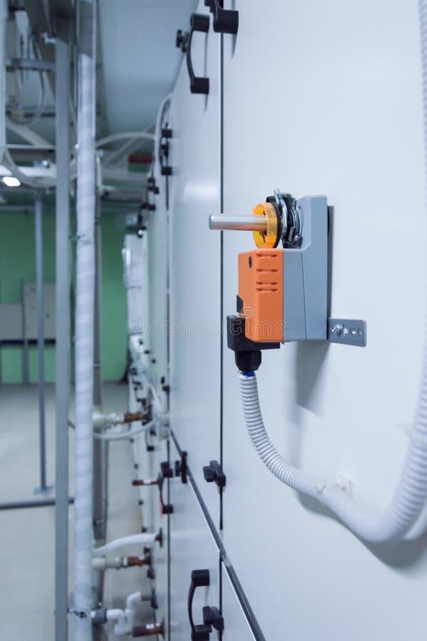 Oranje industriële vochtigere actuator nstalled op het industriële grijze lichaam van de ventilatieeenheid Zachte nadruk stock foto