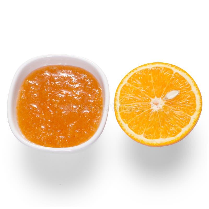 Oranje jam in een witte kom met oranje fruit stock fotografie