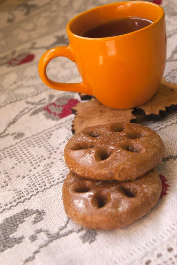 Oranje kleikop met koekjes stock afbeeldingen