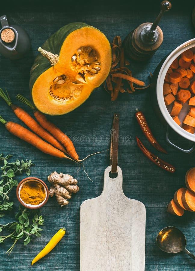 Oranje kleuren kokende ingrediënten rond scherpe raad Pompoen, wortelen, bataten, kurkuma, Spaanse peper en vers kruiden royalty-vrije stock foto's
