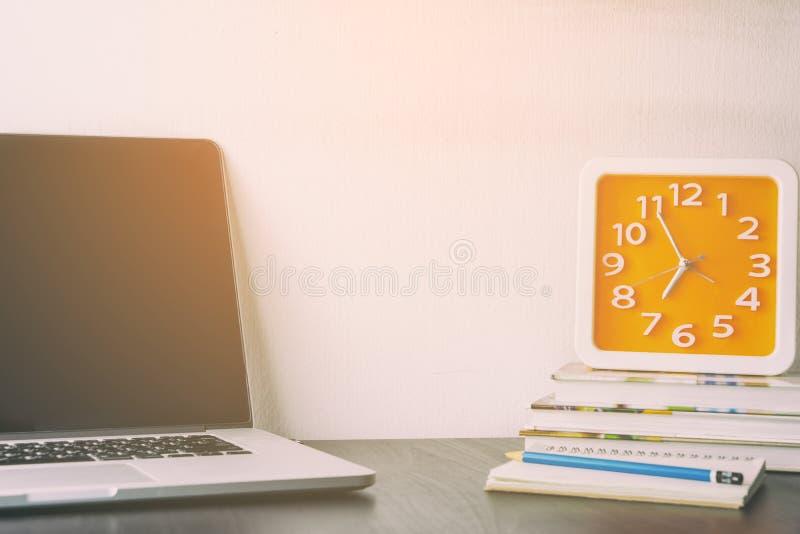Oranje Klok op laptop van de bureaulijst royalty-vrije stock afbeeldingen