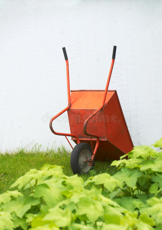 Oranje kruiwagen op gras royalty-vrije stock afbeeldingen