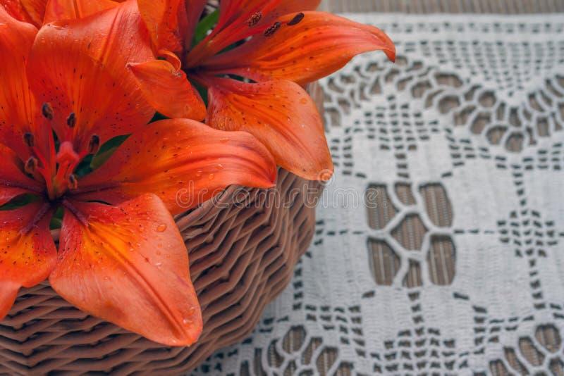 Oranje leliebloemen in een mand stock foto's