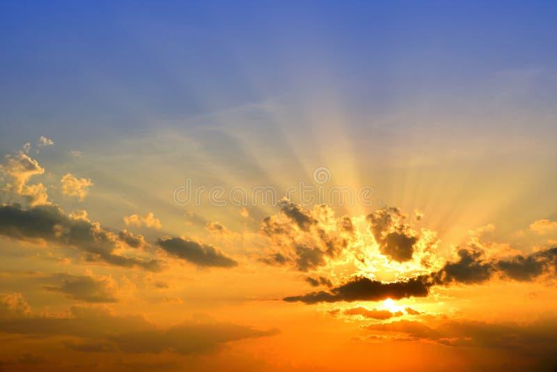 Oranje licht met zonstralen en donkere wolken op hemel stock foto