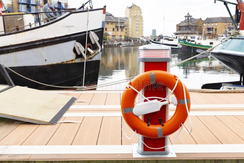 Oranje lifebelt bij haven stock foto